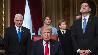Barron Trump stands with his mother Melania as President Donald Trump prepares to formally sign his cabinet nominations into law.