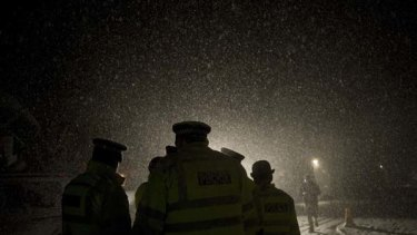 Police officers wait in heavy snow  outside Ellingham Hall, the bail address of WikiLeaks founder Julian Assange.