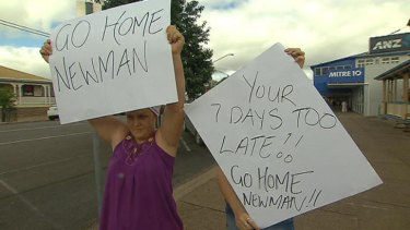Angry Gayndah residents hold up signs as Premier Campbell Newman visits the town.