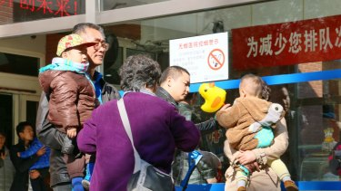 Families with young children gather outside a paediatric hospital in central Beijing.
