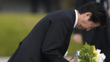 Japanese Prime Minister Shinzo Abe bows as he lays a wreath during the Hiroshima Peace Memorial Ceremony at Hiroshima Peace Memorial Park on August 6, 2016.