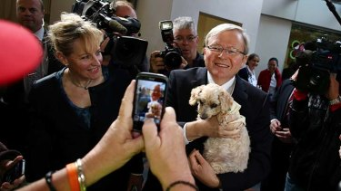 Even puppies enlisted to the cause: Rudd cuddles Precious at a Perth railway station on Friday.
