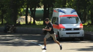 A local resident runs past an ambulance and separatist fighters during the battle for the airport.