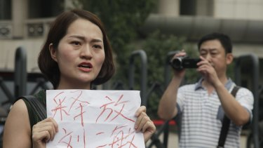 "Li Wenzu, wife of imprisoned lawyer Wang Quanzhang, holds a sign that reads ""Release Liu Ermin"" outside the Tianjin court. Liu Ermin is the wife of one of the arrested activists."