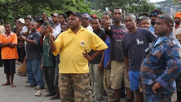 Soldiers and supporters watch Peter O'Neill march on Government House in Port Moresby.