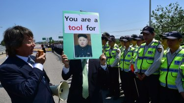 A South Korean conservative activist holds a placard showing a portrait of North Korea's leader Kim Jong-Un as policemen surround him during a protest against the border crossing by the women.