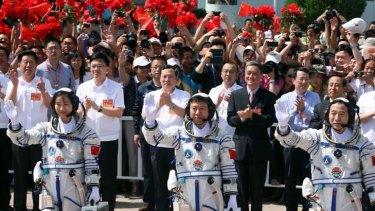 National heroine ... Major Liu Yang waves to the crowd alongside fellow astronauts Liu Wang and mission commander Jing Haipeng.