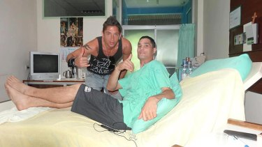 Sean with a visitor in hospital in Thailand.