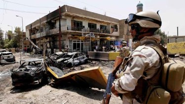 An Iraqi Army soldier stands guard at the site of a car bomb attack in Baghdad.