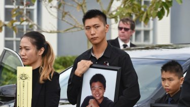 Jason Wang, centre, holds a picture of his brother Peter, along with his younger brother, Alex, after his brother's funeral.