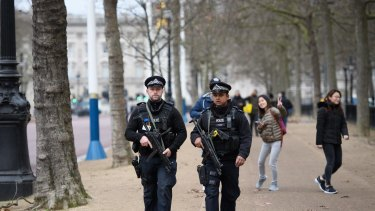 Armed police officers patrol The Mall in front of Buckingham Palace ahead of the Changing of the Guard ceremony.