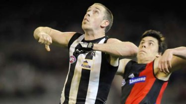 Collingwood's Nick Maxwell and Essendon's Angus Monfries fly for the ball last night.