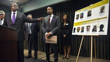Nine and counting: Brooklyn District Attorney Ken Thompson, left, points to a time-line photo display of individuals exonerated in wrongful conviction cases, as he speaks during a press conference.