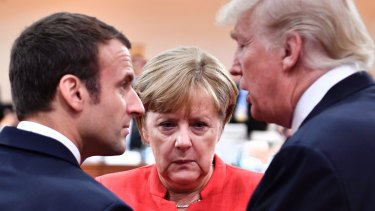 France's Emmanuel Macron, Germany's Angela Merkel and US President Donald Trump engage in conversation at the start of the first working session of the G20 on Friday.