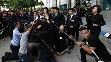 Thailand's former Prime Minister Yingluck Shinawatra talks to the waiting media while being watched by Thai security on Tuesday.