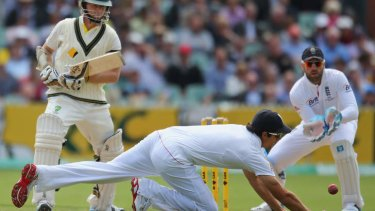 Alastair Cook goes after the ball as Steve Smith watches on.