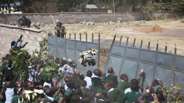 Kenyan children push down the wall leading to a playground during a protest in January.