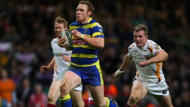 Joel Monaghan (c) makes a break for the Warrington Wolves.