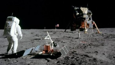 Buzz Aldrin stands beside a seismometer on the moon.