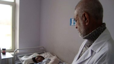 A doctor with 17-year-old Afghan girl Mumtaz, who was  attacked with acid.