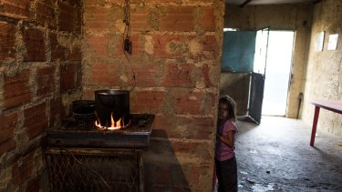 A child in her house in Barlovento waits for lunch, which consists of only boiled yam. Food sold in the black market can be 1000 per cent higher than what it cost in government-regulated grocery stores.