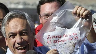 """Chile's President Sebastian Pinera holds up a plastic bag containing a message from the trapped miners that reads in Spanish """"We are ok in the refuge, the 33 miners"""""""