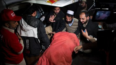 Pakistani volunteers move remains of plane crash victims to a mortuary at a hospital, in Abbottabad.