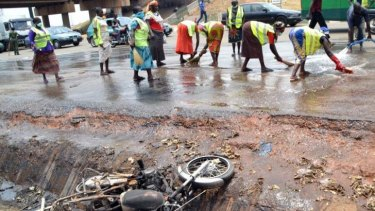 Week of violence ... Nigerian workers clean the site of a bomb blast in Abuja ripped through a packed bus station killing at least 75 and injuring 141. The explosion was blamed on Islamic extremist group Boko Haram.