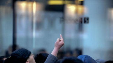 A Chinese man gestures as thousands of customers queue up outside an Apple store in Beijing.