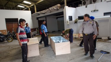 Workers from Abadi Funeral Homes prepare two wooden boxes to carry the coffins of Myuran Sukumaran and Andrew Chan home to Australia.