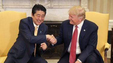 Trump demonstrates his technique with Japanese Prime Minister Shinzo Abe, to the latter's obvious discomfort.