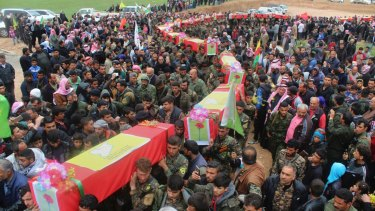 Fighters from the predominantly-Kurdish Syrian Democratic Forces carrying the coffins of their comrades, who were killed in an airstrike in mid-April.