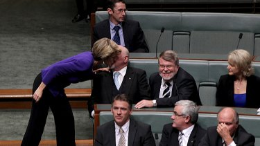 Deputy Opposition Leader Julie Bishop gives Liberal MP Mal Washer a kiss after he crossed the floor to vote with the government. He eventually voted with the opposition.