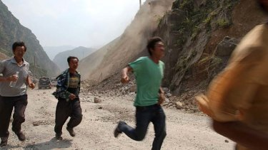 Danger ... men run to avoid falling rocks during an aftershock.