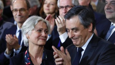 Conservative French presidential candidate Francois Fillon applauds while his wife Penelope looks on.
