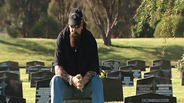 "Geoff ""Snake"" Campbell, a former member of the Bandidos bikie gang, sits on the grave stone of one of his brothers - two of which died at Milperra in the Father's Day massacre."