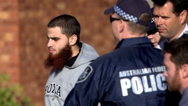 A man is led away by police in Seabrook as simultaneous raids are carried out across Melbourne on Tuesday morning.