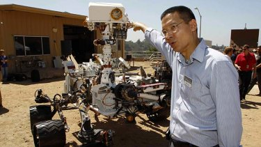 Guidance, Navigation, and Control Systems Manager and Deputy Surface Phase Lead Steve Lee points to the remote sensing mast which includes navigation cameras and a ChemCam laser on an engineering model of NASA's Curiosity Mars rover