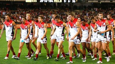 Shell-shocked: Melbourne players leave the MCG after a record belting from Essendon.