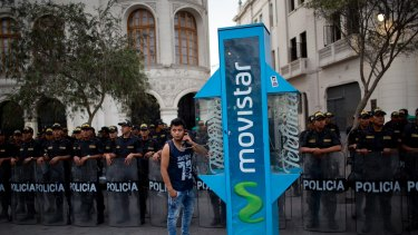 Police stand guard as a man makes a phone call during a protest in Lima calling for justice in the Odebrecht corruption scandal.