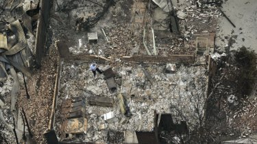 A policeman walks through the burnt ruins of Marysville police station.