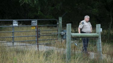 An officer guards the entrance where Devin Patrick Kelley lived.