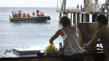 Locals at Flying Fish Cove have a ringside seat as asylum seekers are taken ashore at Christmas Island.