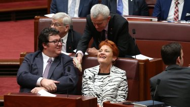 Senator Malcolm Roberts offers a bag of cashews to Senator Pauline Hanson and George Christensen during the opening of the 45th Parliament on Tuesday.