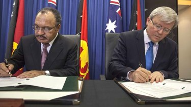 Done deal: Papua New Guinea's Prime Minister Peter O'Neill and Australian Prime Minister Kevin Rudd sign an agreement over asylum seekers on July 19, 2013.