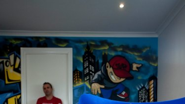 Commercial graffiti artist Ashley Goudie (left, rear) and Oscar Greenshields, 10, (right) in Oscar's Eynesbury bedroom with the skater boy mural Goudie painted.