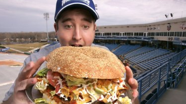 Hungry ... Josh Kowalczyk, an intern with the West Michigan Whitecaps, tries out the 4800 calorie burger.