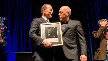 Tony Abbott hands Richard Flanagan the Prime Minister's Literary Award for fiction.