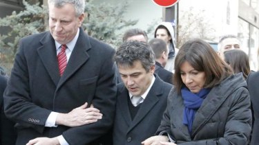 New York city mayor Bill de Blasio, left, Paris mayor Anne Hidalgo, right, and Patrick Pelloux, centre, a staff member of <i>Charlie Hebdo</i> newspaper, outside <i>Charlie Hebdo</i> offices, in Paris, on January 20.