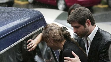 Relatives of Karen Berendique cry over the hearse carrying her coffin.